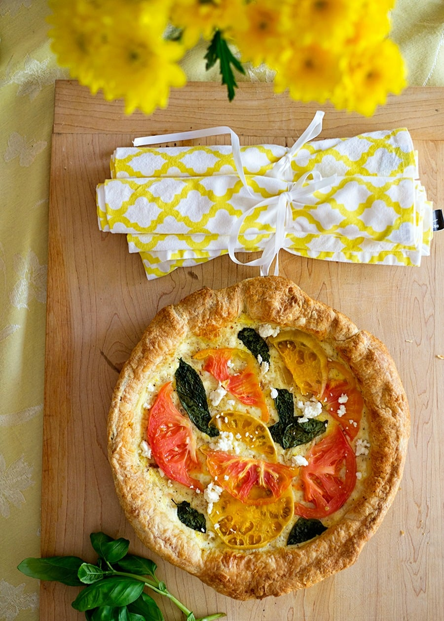 tomato and cheese tart with yellow flowers and yellow print cloth napkins