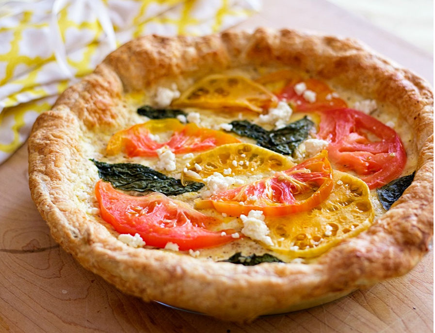 tomato and cheese tart on butcher block tray