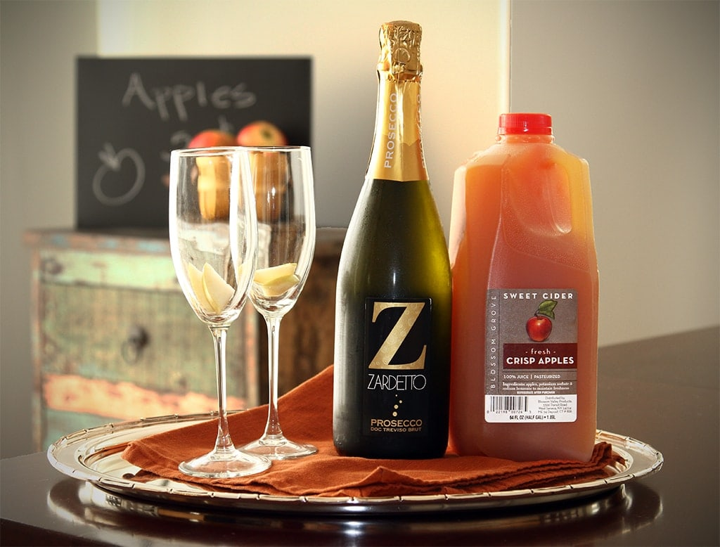 Apple Cider Mimosa supplies - champagne flutes, sparkling wine and apple cider sitting on a tray