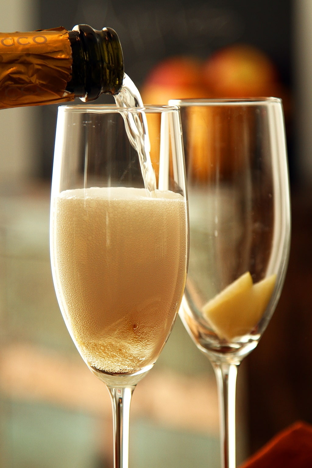 pouring prosecco into glass to make apple cider mimosa drinks