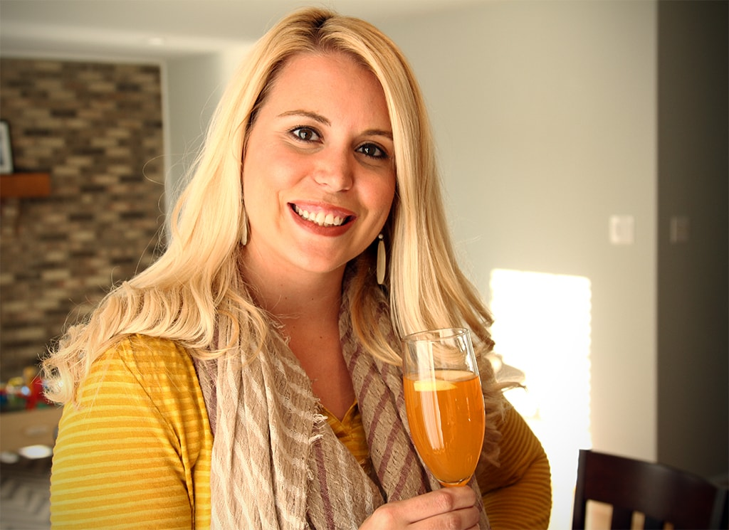 Blonde woman in yellow top and scarf holding a cocktail in a champagne flute