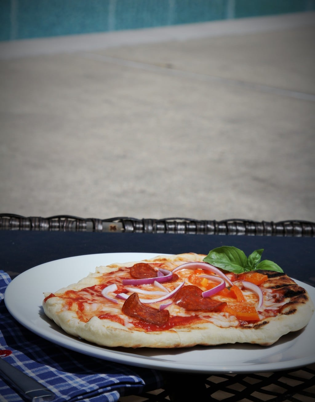 grilled pizza on a white plate by a pool