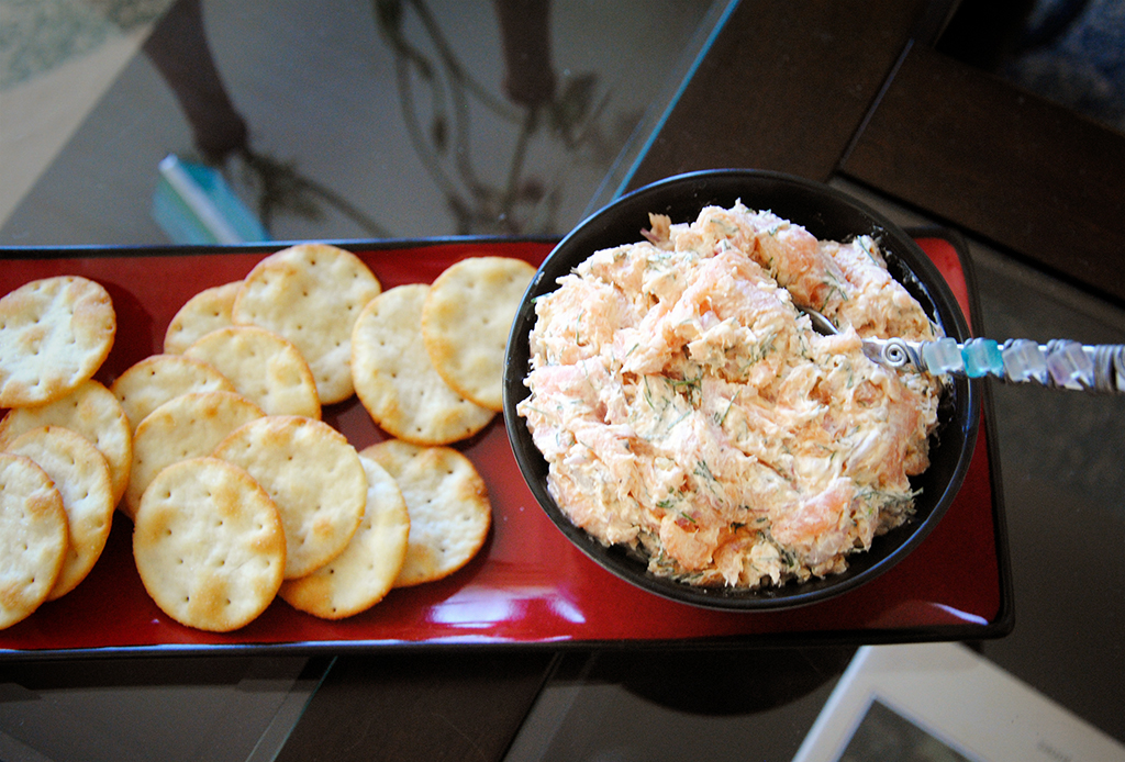 Smoked Salmon Spread Recipe in a bowl on a red plate with pita rounds