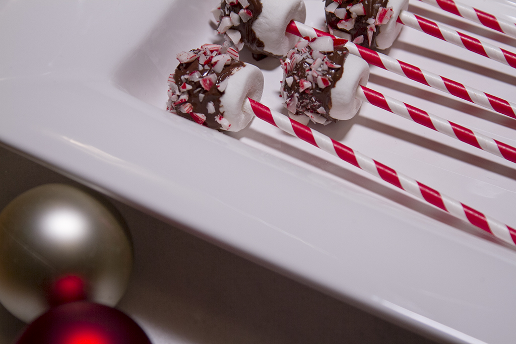 candy cane and chocolate covered marshmallow pops on white tray
