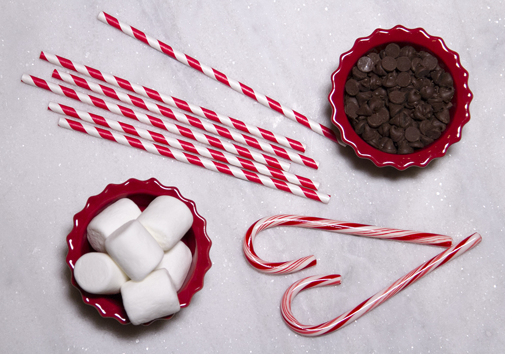 chocolate chips, red and white striped straws, marshmallows and candy canes on white marble