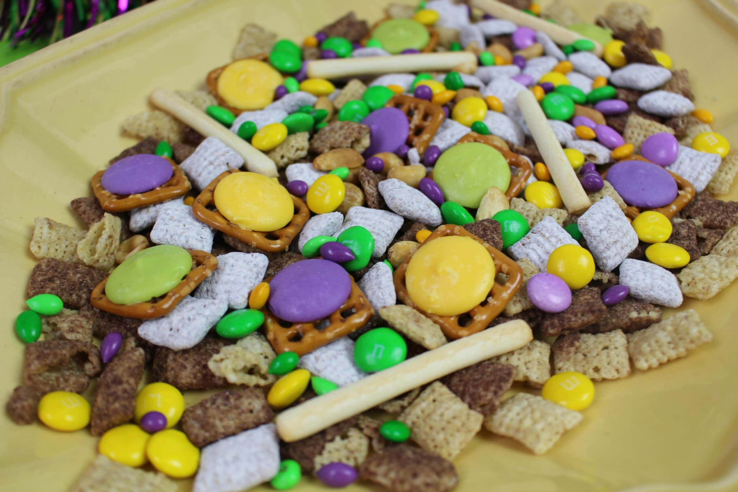 purple, green and yellow pretzel, chocolate and Chex cereal snack mix on yellow plate