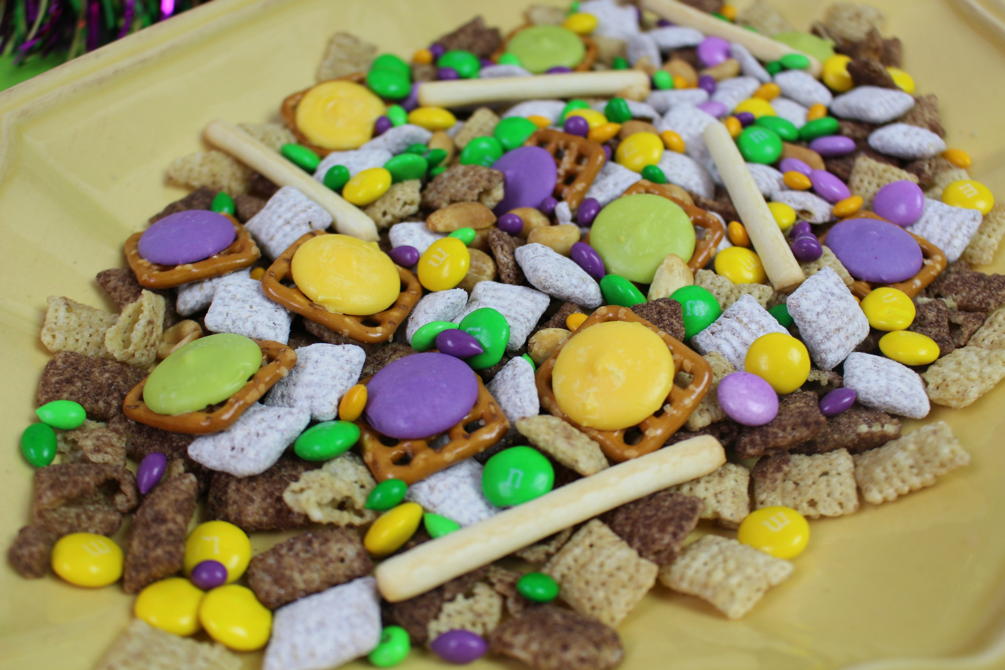 purple, yellow and green pretzel, chocolate and chex cereal snack mix on yellow plate