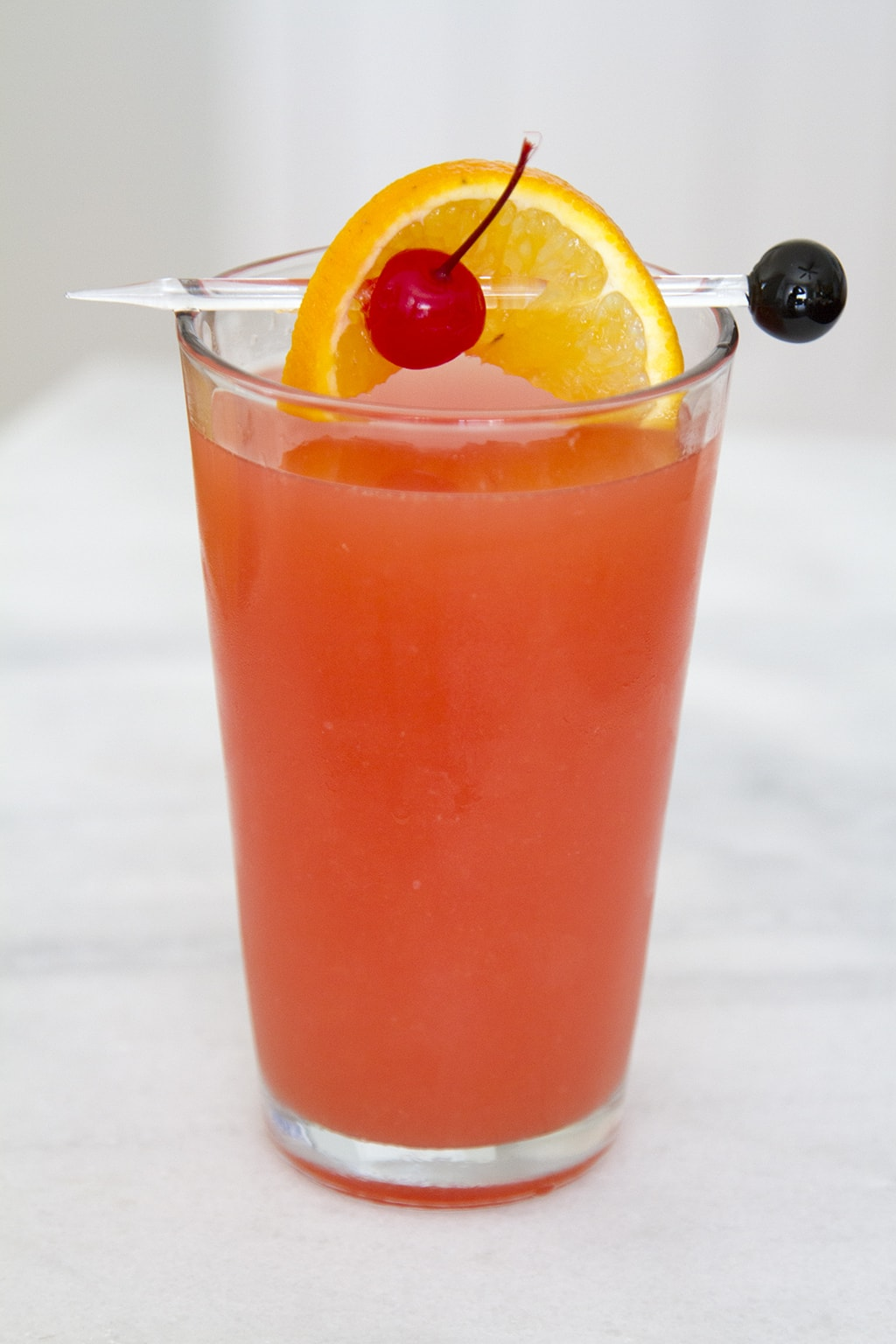 Hurricane drink with cherry and orange garnish
