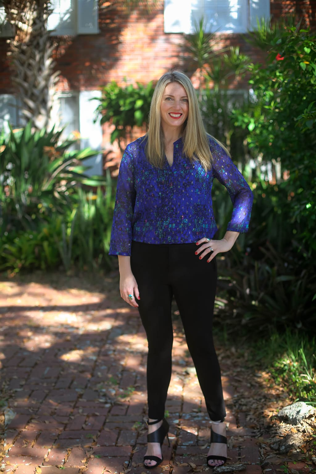 What to Wear To A Holiday Lunch - holiday lunch outfit. Blonde woman wearing blue blouse with black leggings paired with black strap heels and turquoise rings.