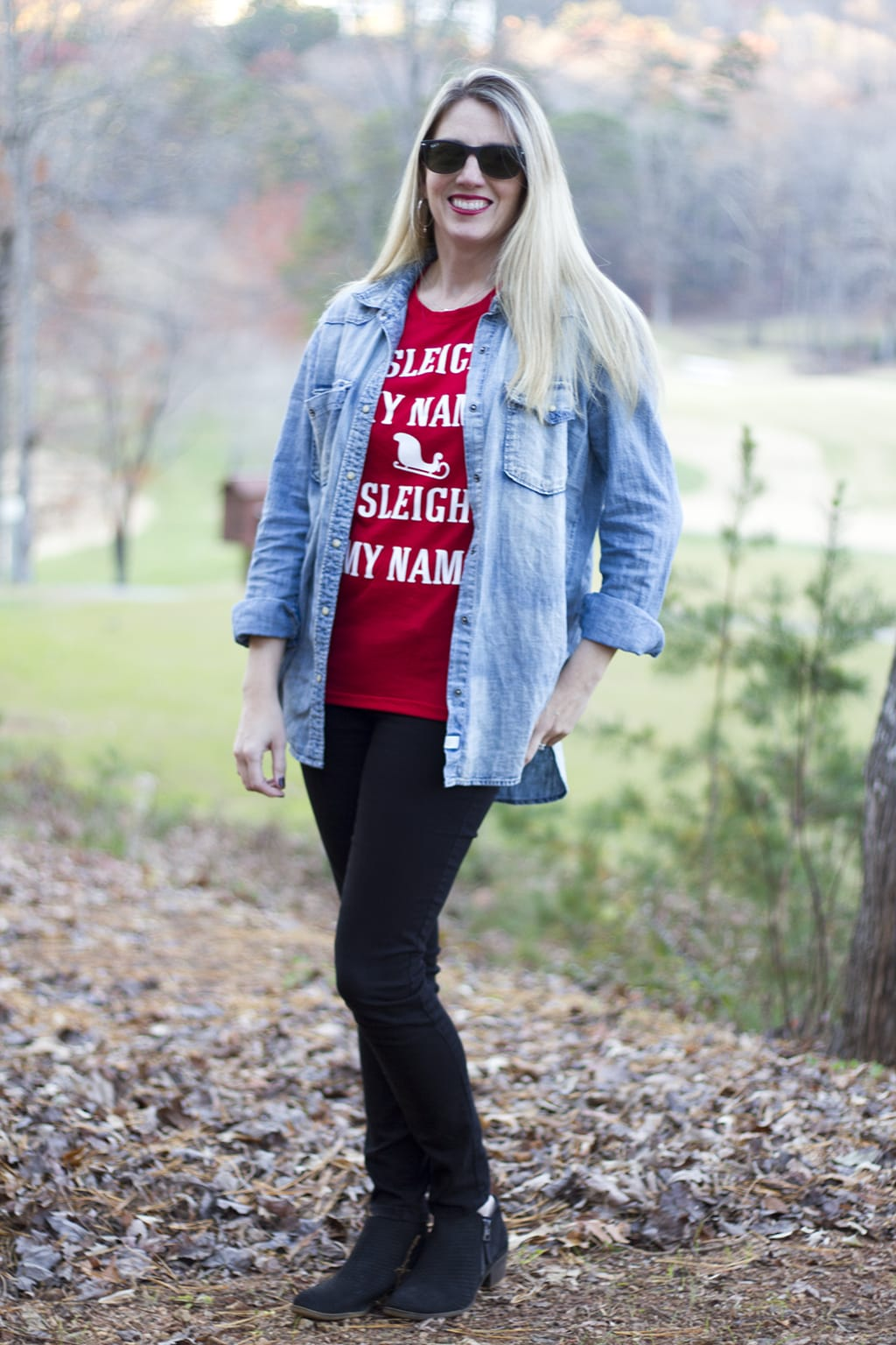 woman with blond hair wearing denim shirt and red graphic holiday tee