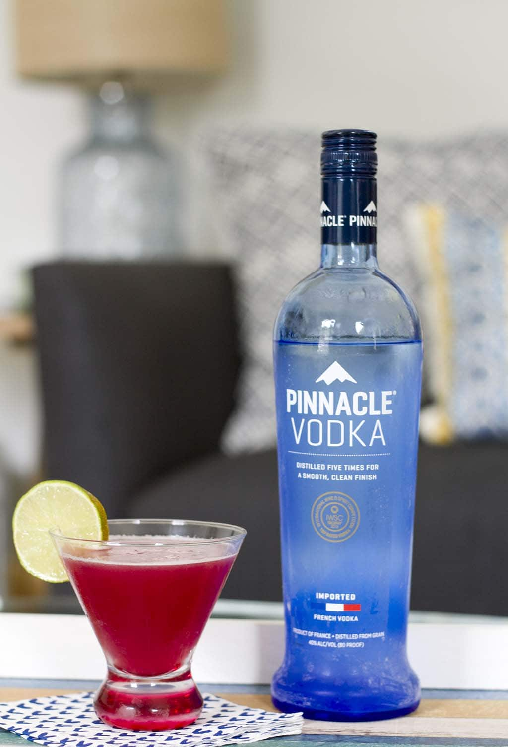 blue bottle of Pinnacle vodka next to red cranberry drink with lime slice on rim on top of white napkin with blue hearts on table in front of blue couch and light blue glass lamp