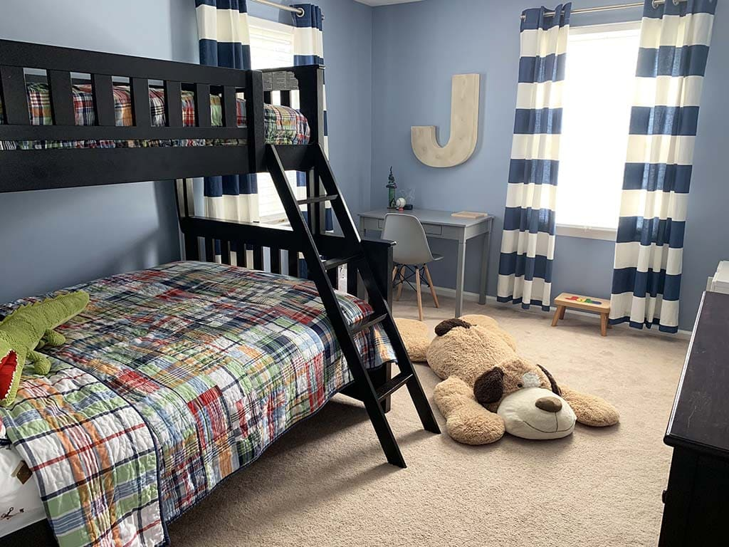Boys updated bedroom with plaid bedding and stuffed animals.