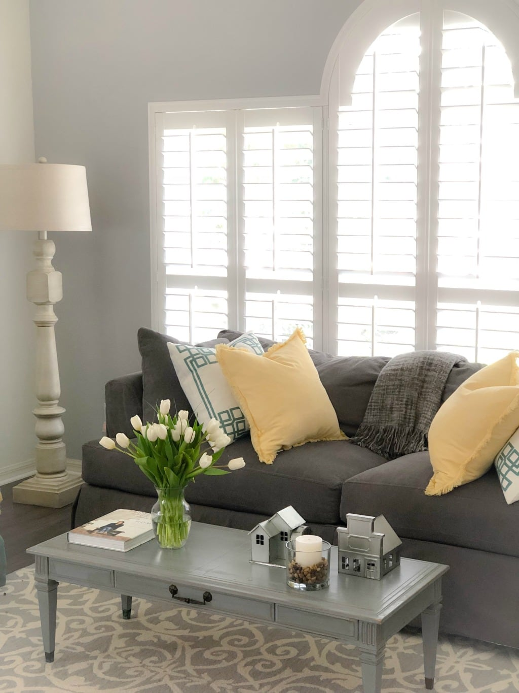 beautiful white plantation shutters in living room with gray furniture