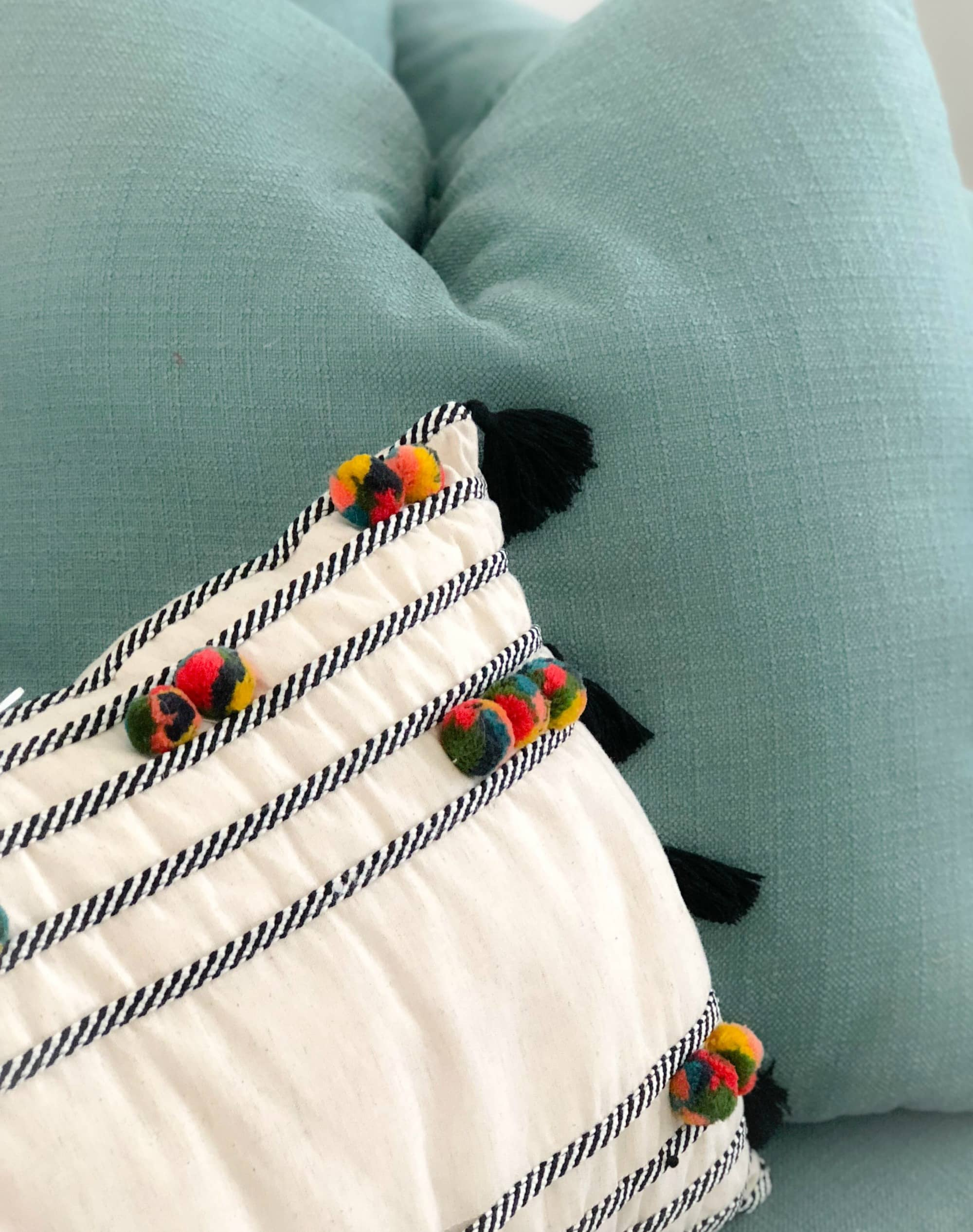 pom throw pillow with fringe on chair