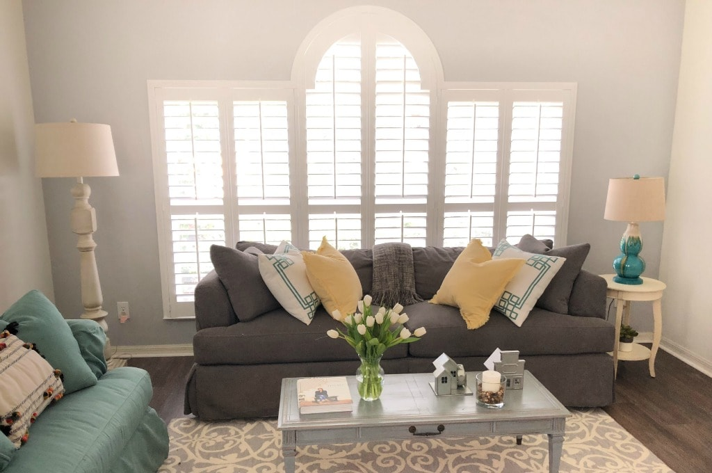 plantation shutters on large statement window in living room