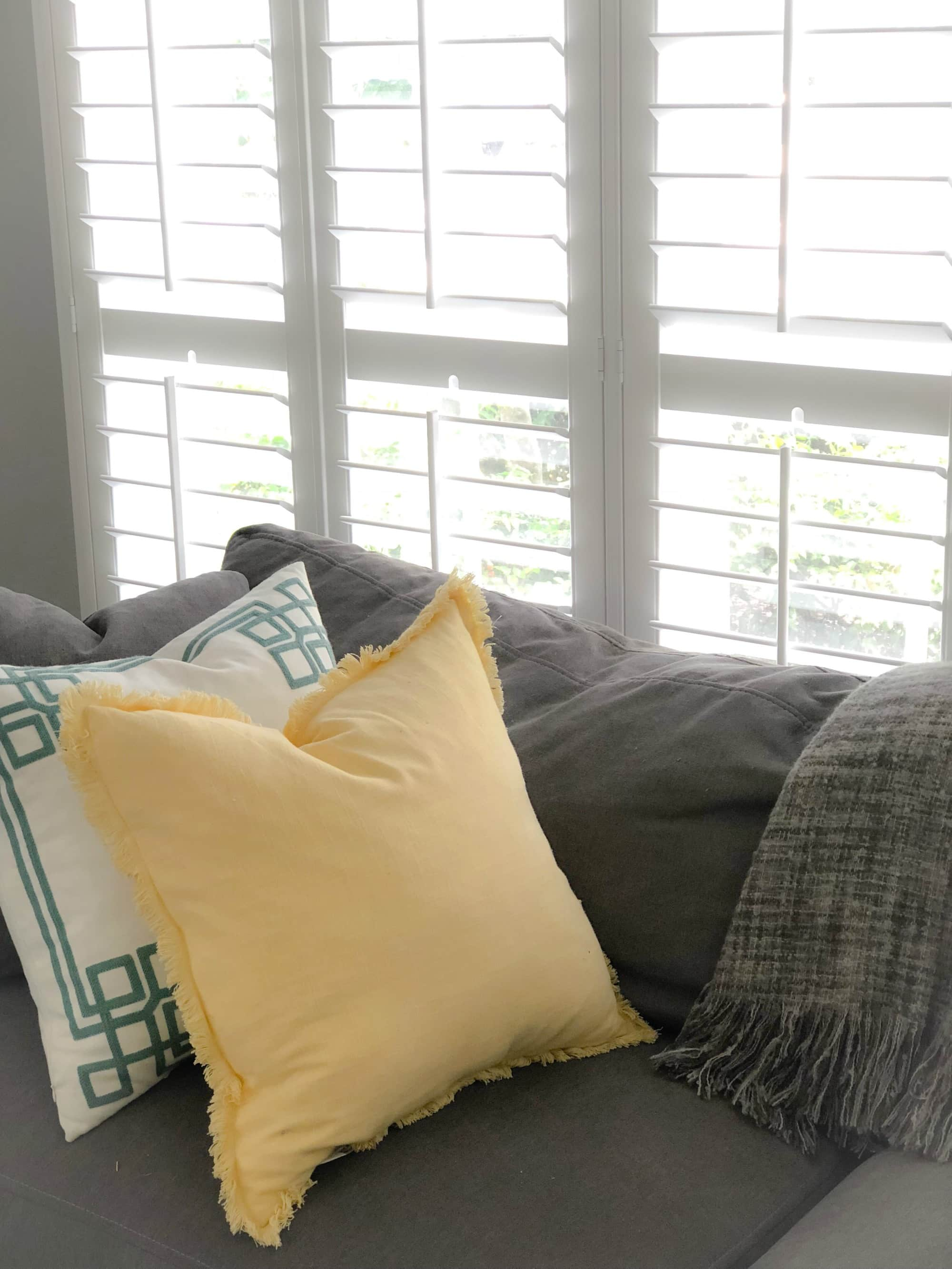 white plantation shutters and gray couch
