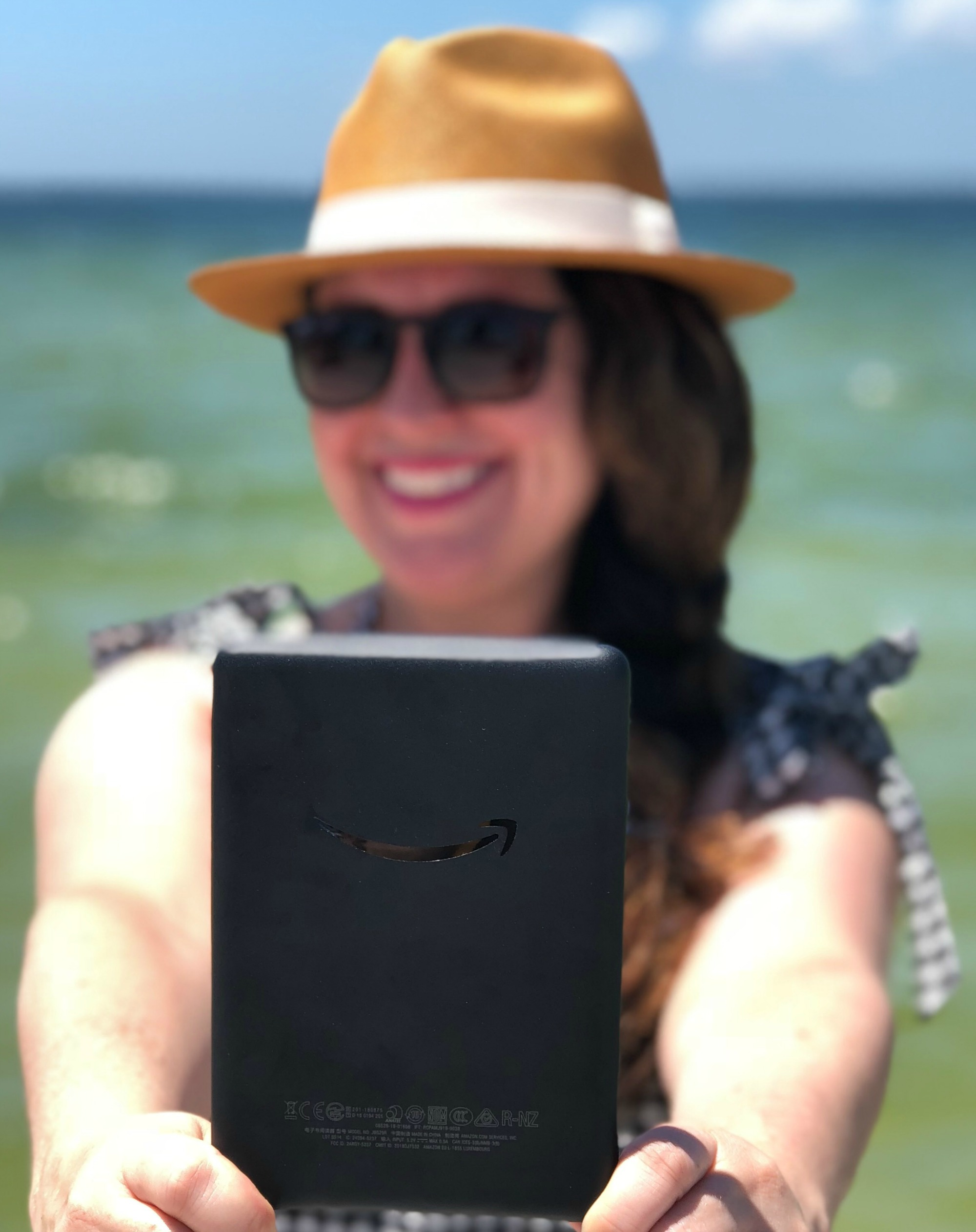 woman holding amazon kindle on the beach