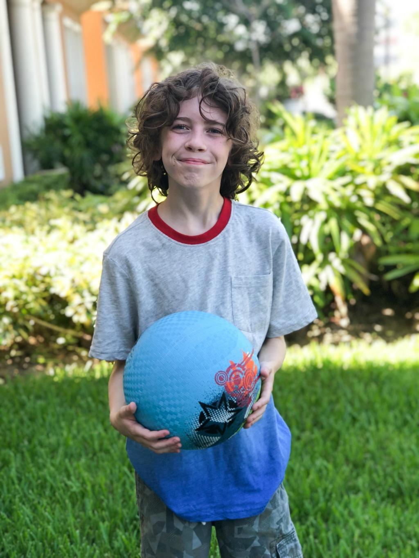 boy playing with kickball