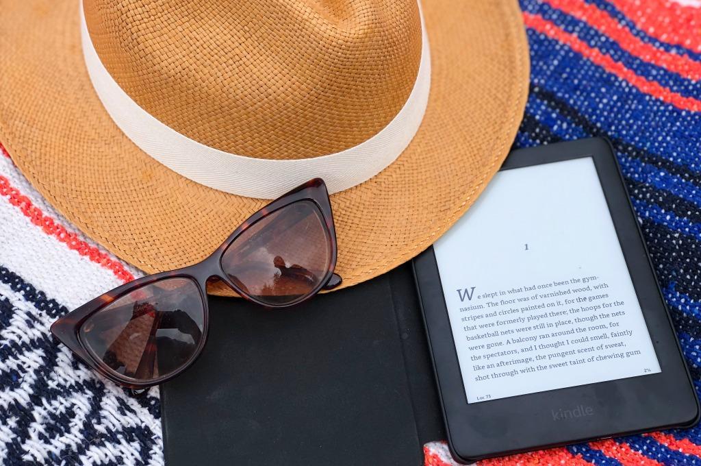 amazon kindle, panama hat and sunglasses on beach blanket