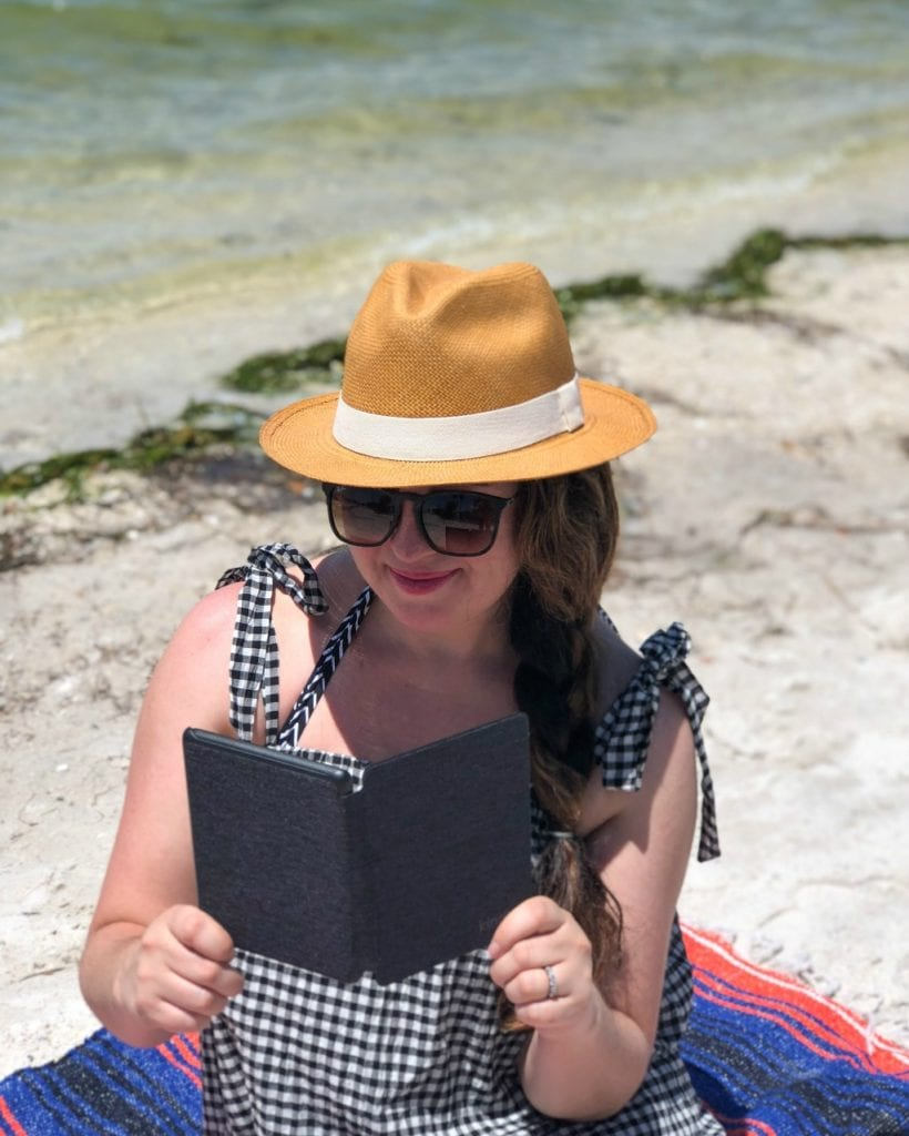 woman reading by the beach