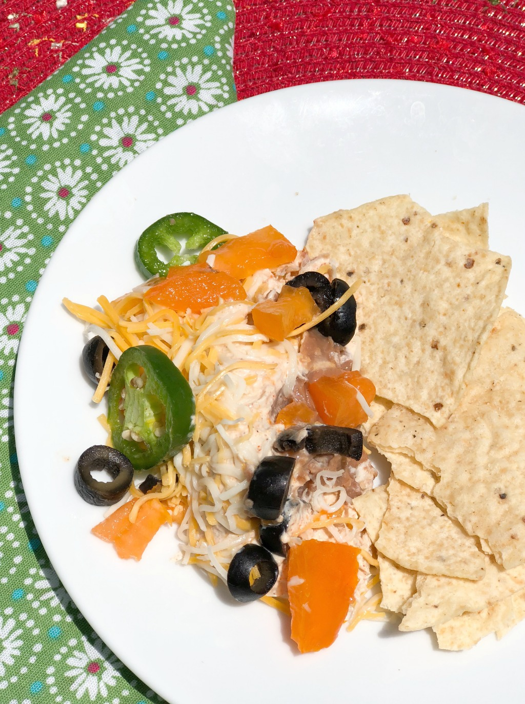 tortilla chips and seven layer dip on white plate