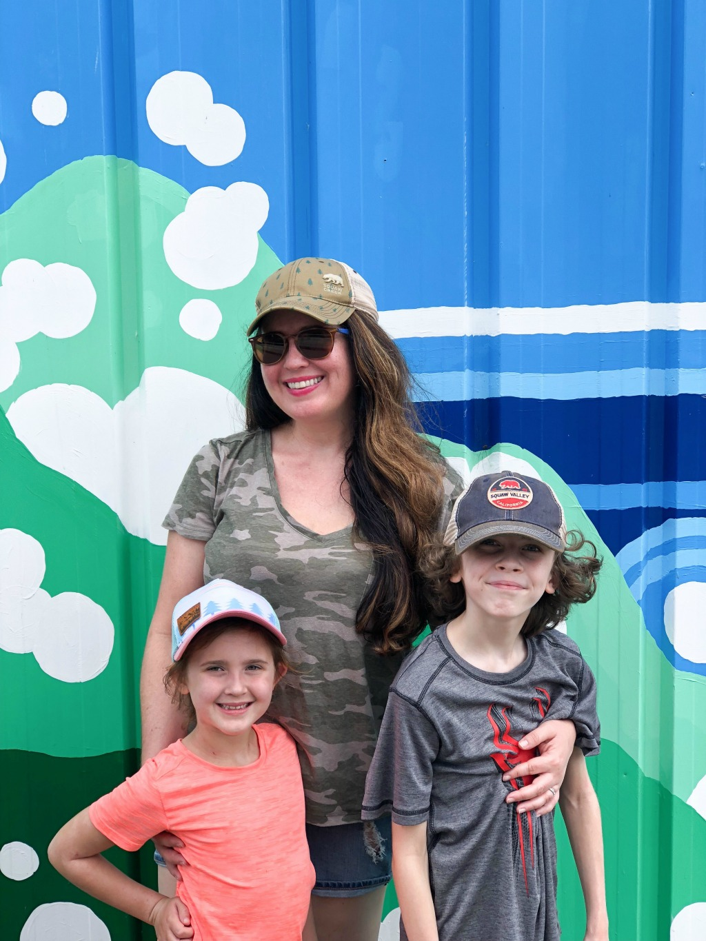 mother and children in front of blue and green mural