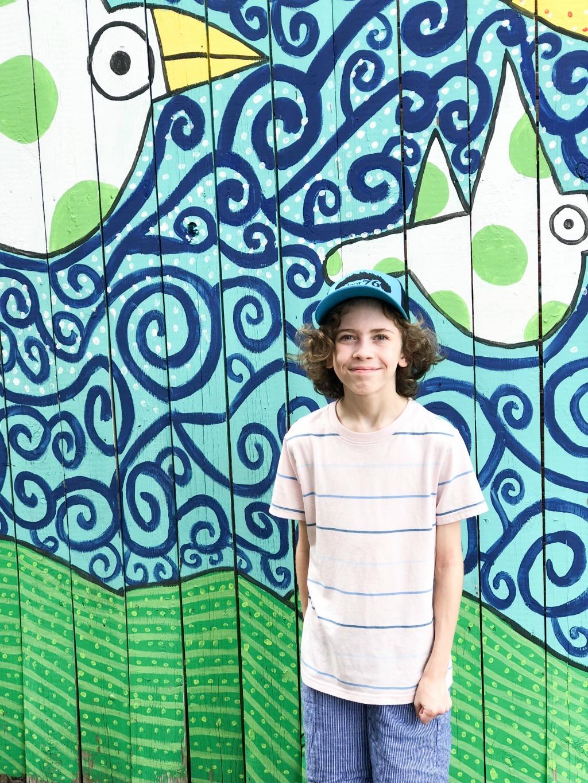 little boy standing in front of bird mural