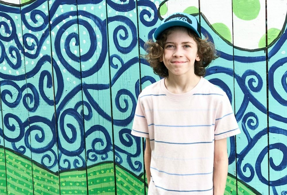 little boy smiling in front of a blue and green mural