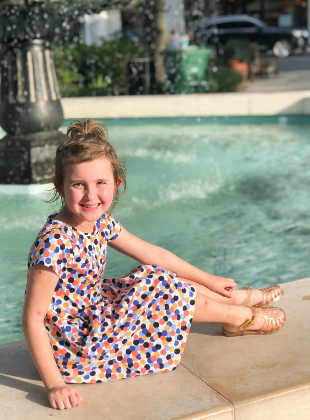 little girl sitting next to a fountain