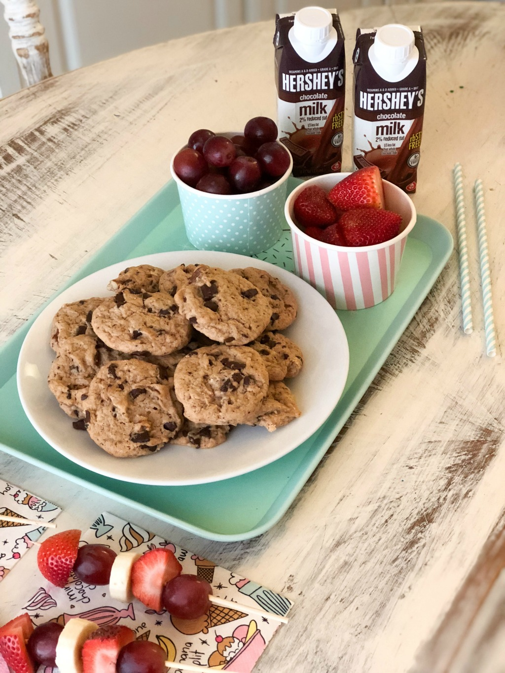 cookies, fruit and hershey's chocolate milk on a white table