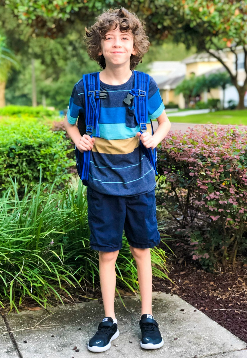 11 year old boy holding his blue backpack in front yard