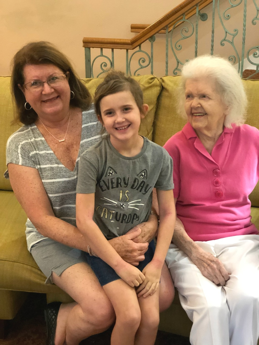 great-grandmother, grandmother and granddaughter sitting on couch
