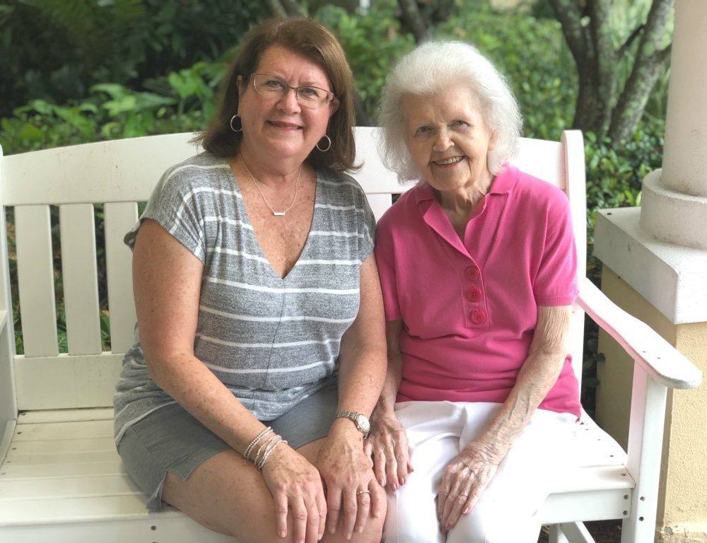 elderly mother and daughter sitting on a white bench