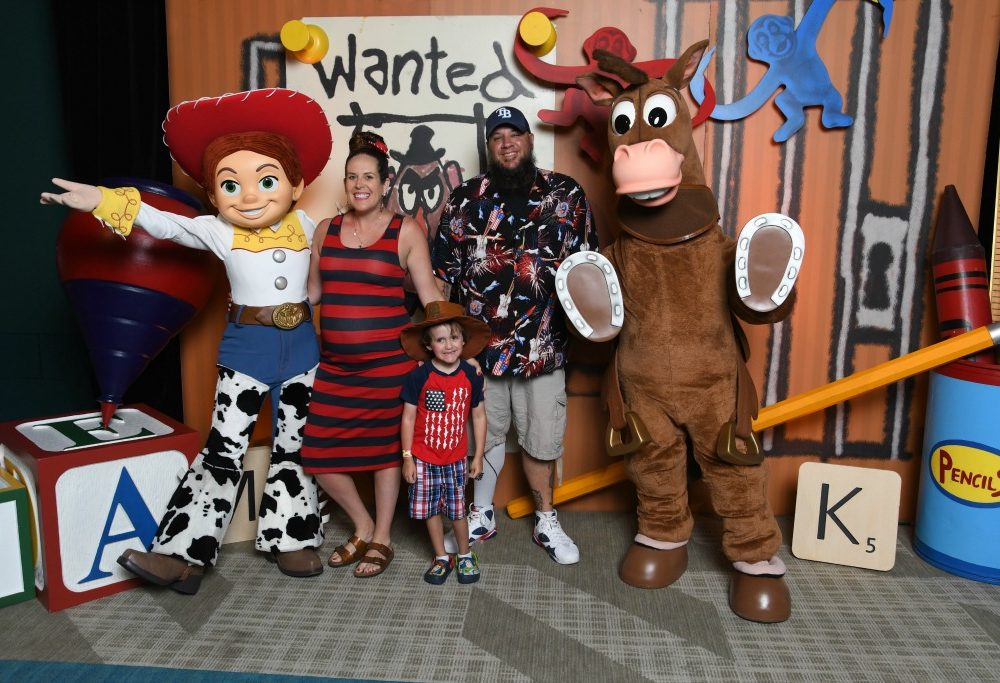 family posing with toy story characters jessie and bullseye