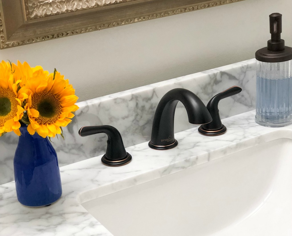 rubbed oil bronze faucet with white marble vanity top