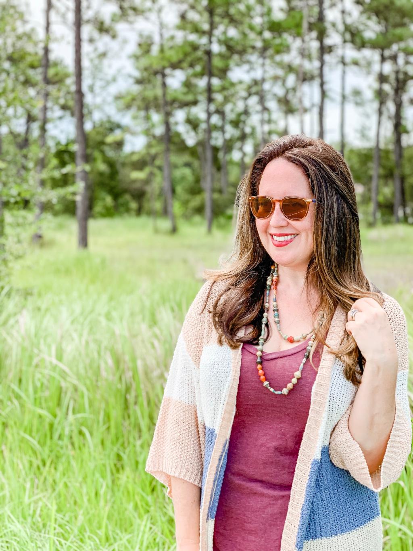 woman wearings striped open cardigan standing in field