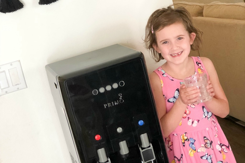 little girl in pink dress standing next to primo water dispenser