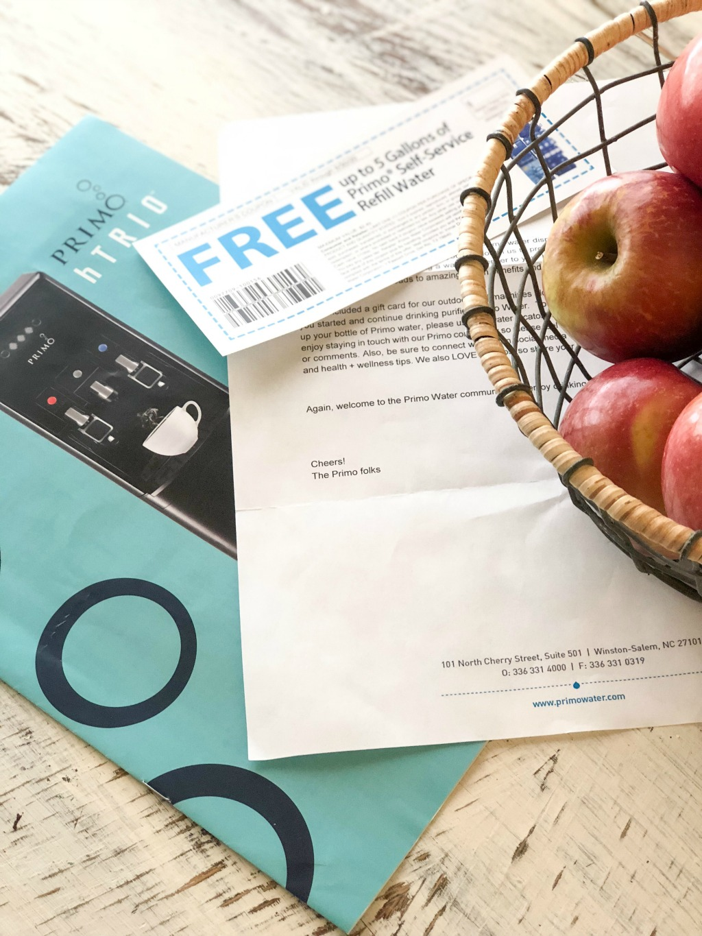 primo water coupons on kitchen table with bowl of red apples