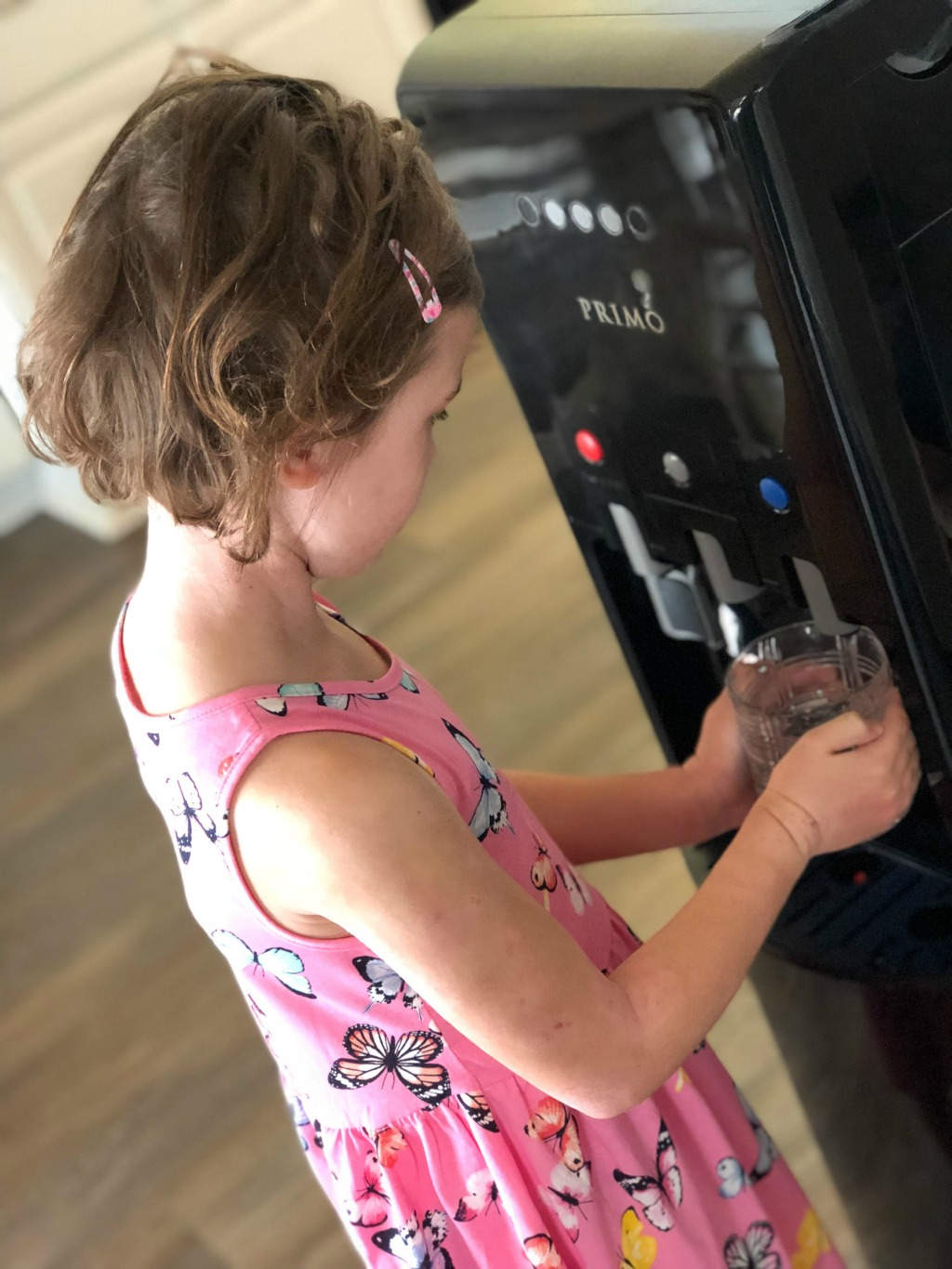 little girl filling up glass of water with water dispenser