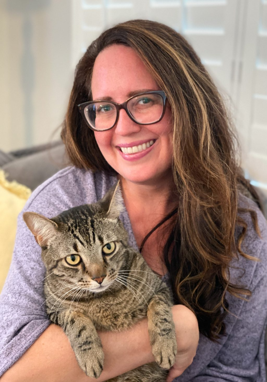 long brown haired woman in glasses holding a striped tiger tabby cat
