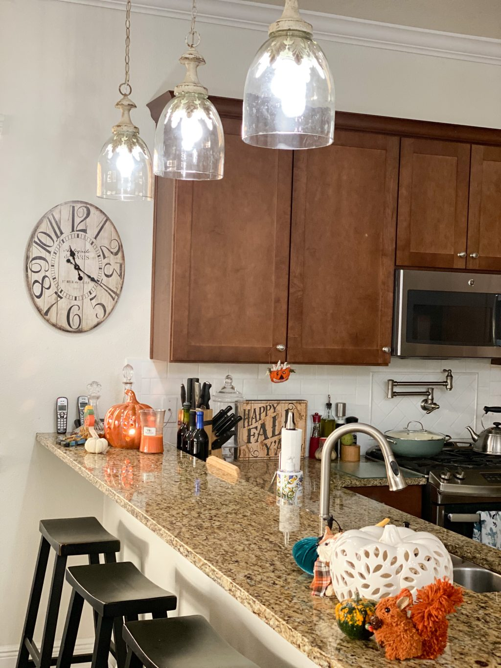 off white distressed pendant lights hanging over brown granite counter
