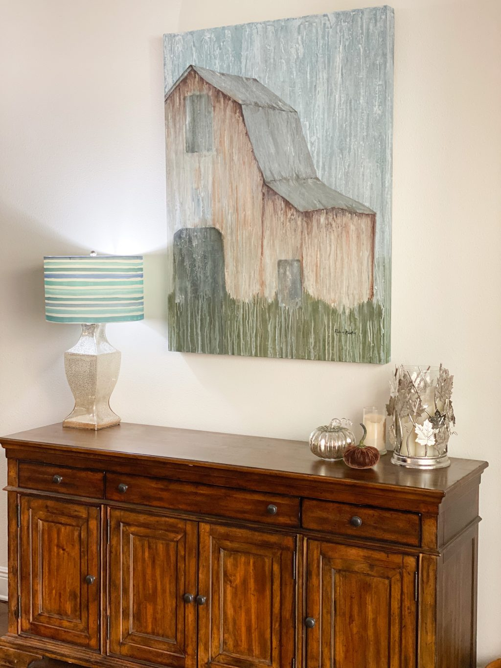 blue farmhouse painting hanging over brown wood console