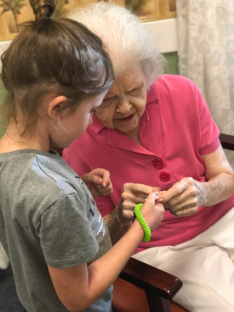 little girl and elderly woman looking at key ring