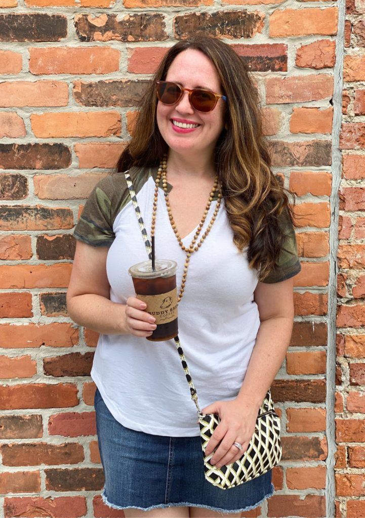 woman holding iced coffee in front of brick wall