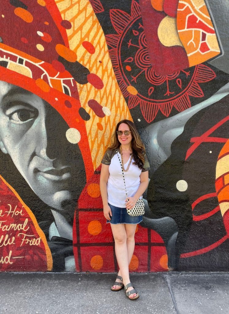 woman standing in front of red and orange mural