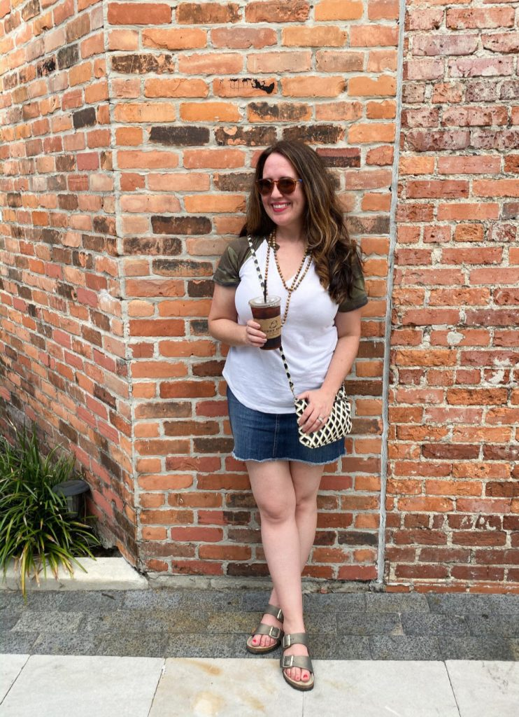 woman wearing camo tee and denim skirt standing in front of brick wall