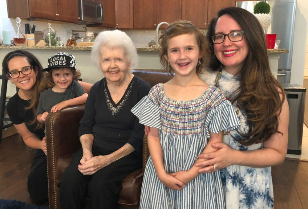 grandmother, grandaughters, great granddaughter and great grandson standing in kitchen with brown cabinets and brown granite