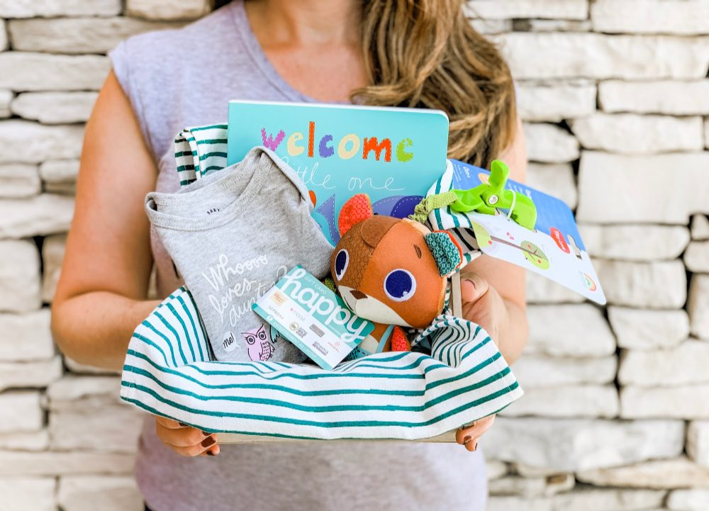 woman holding new mom gift with baby onesie, gift card, board book and plush squirrel toy
