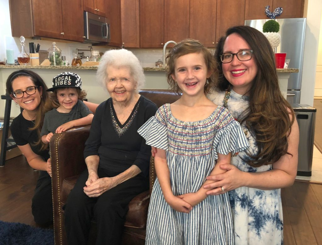 grandmother, her grandaughters and their children sitting in kitchen