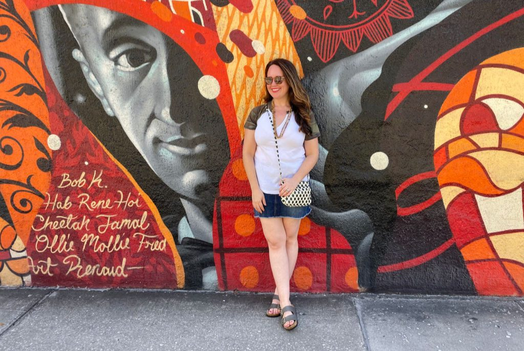 woman standing in front of orange and red mural in tampa